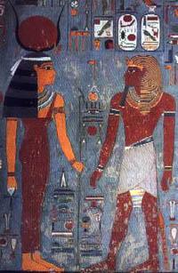 Horemheb ante Hathor, que porta el cetro uas en una mano y el anj en la otra. La diosa aparece en su representación característica, como mujer con los cuernos de vaca y el disco solar entre ellos. Bajorrelieve policromado. Tumba de Horemheb (KV57) - Valle de los Reyes, XVIII Dinastía